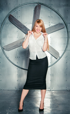 steely: Beautiful smiling blond woman turning up collar of her white blouse standing in front of big propeller on a steely wall Stock Photo