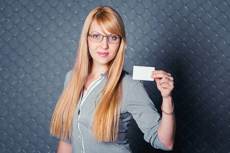 chain link fence: beautiful young smiling woman with blond long hair wearing glasses standing against chain link fence holding blank business card Stock Photo