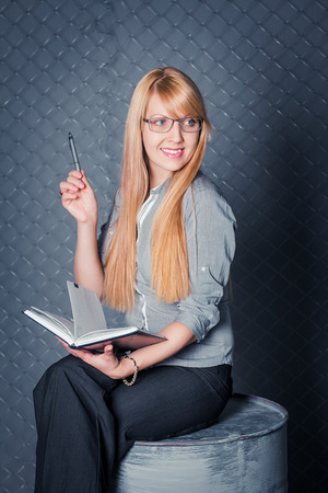 chain link fence: Attractive smiling businesswoman holding diary sitting on the iron barrel in front of chain link fence