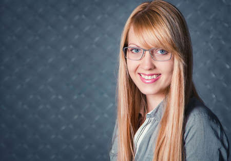 chain link fence: Portrait of beautiful young smiling woman with blond long hair wearing glasses posing against chain link fence Stock Photo