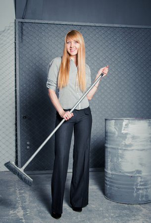 charwoman: Pretty smiling charwoman standing in industrial area with broom in her hands Stock Photo