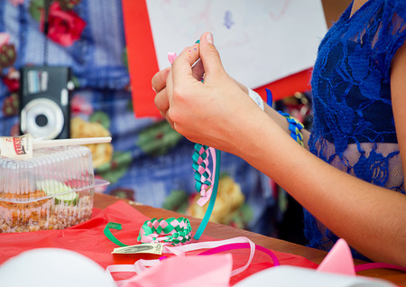 ZAPOROZHYE, UKRAINE - SEPTEMBER 5, 2015. Bracelets braiding workshop during family festival organized by Charity Fund Childs Smile for citizens and Donetsk refugees, financed by USAID Editorial