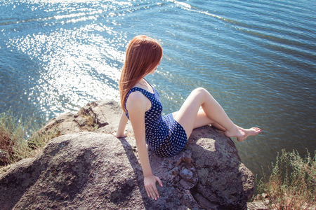 beautiful sad: Beautiful sad and pensive woman with long red hair sitting on the cliff edge above the river looking down on water surface