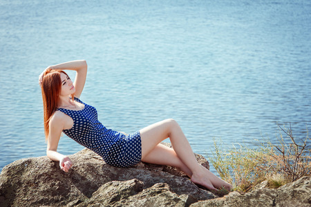 Pretty young redhaired woman in short dress laying on the cliff above the river enjoying warm sunny summer day Stock Photo