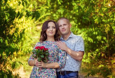 rosas rojas: Feliz joven amante de abrazos y posando en el parque con el ramo de rosas rojas Foto de archivo