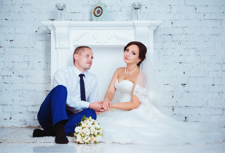 romantic flowers: bride and groom sitting near fireplace on their wedding day Stock Photo