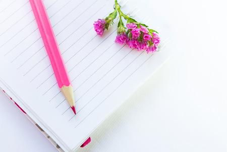 espiral: cuaderno vac�o, l�piz de color rosa y flores sobre un fondo blanco textil