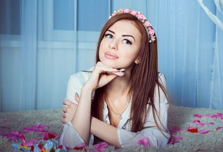 sensual girl: Beautiful young smiling woman  in white dress with flowers wreath in her hair laying on a rug with pink and red rose petals