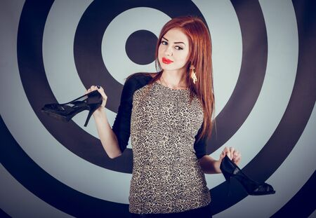 red lips: studio portrait of beautiful smiling sexy woman with stylish makeup and red lips holding her black high-heeled shoes standing in front of target background Stock Photo