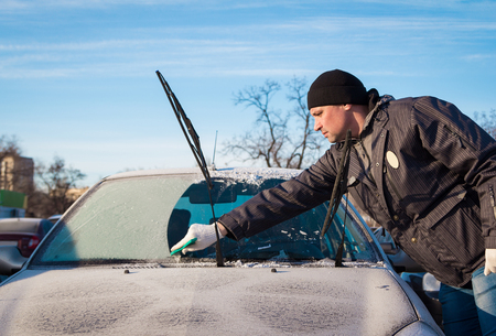 Man scraping frozen front windshield of his car