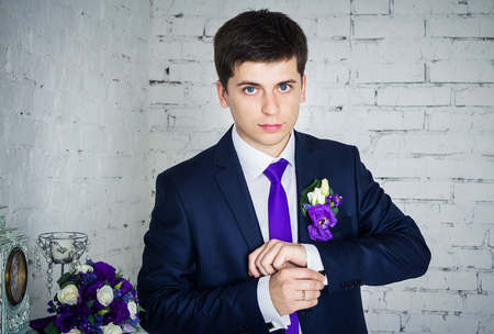 cufflinks: Studio portrait of young handsome brunette  groom wearing blue suit and purple tie clasping cufflinks Stock Photo