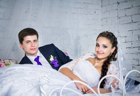 blue romance: Attractive smiling happy bride and groom in ceremonial clothing laying on a bed