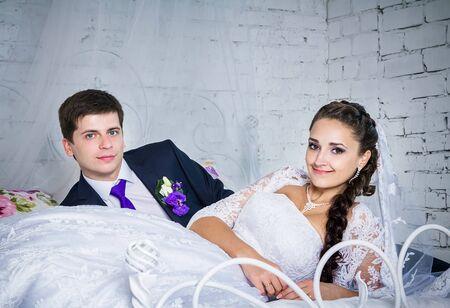 femme romantique: Attractive souriante mari�e heureuse et mari� dans c�r�monielle v�tements pose sur un lit
