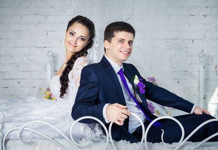 marido y mujer: Atractiva sonrisa feliz novia y el novio en ropa ceremonial que se sienta en una cama