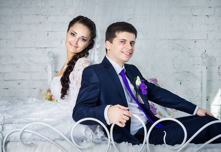 blue romance: Attractive smiling happy bride and groom in ceremonial clothing sitting on a bed