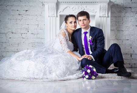 femme romantique: jeune mari�e et le mari� heureux assis sur le plancher pr�s de chemin�e le jour de leur mariage