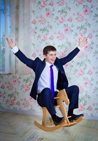 destress: Happy childish young man in business suit riding toy wooden horse. Adult acting like a child concept