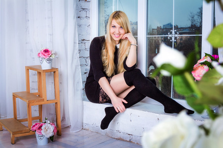 Beautiful young smiling woman with long blond hair wearing stockings and short black dress with lacy skirt sitting on the window sill in a room decorated by flowers