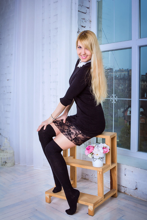 Beautiful young smiling woman with long blond hair wearing stockings and short black dress with lacy skirt sitting on the wooden stepladder near the window