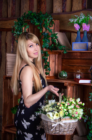 artificial hair: Beautiful young smiling woman with long blond hair  wearing casual dress standing near vintage wooden shelf with books and bouquets in glass vases, holding wicker basket with artificial flowers Stock Photo