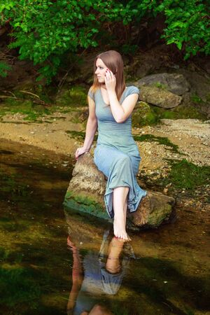 long feet: Attractive young woman with long hair wearing casual dress sitting on the rock with feet in a weedy pond water