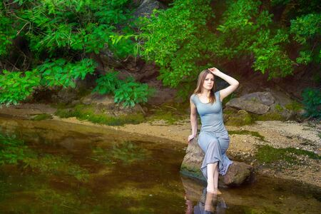 long feet: Beautiful young woman with long hair wearing casual dress sitting on the rock with feet in a weedy pond water