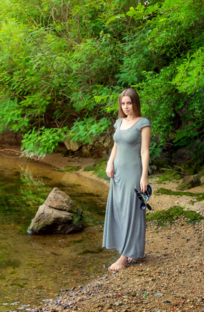 barefeet: Beautiful young woman with long hair wearing casual dress standing barefoot on the river bank holding slippers