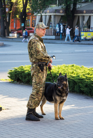 disclose: ZaporizhiaUkraine- May 19, 2016: Dog handler, explosives expert  in uniform with dog guarding public safety during  celebration of traditional Ukrainian embroidered clothes, known as vyshyvanka  day, celebrated in all regions of Ukraine every third Thurs