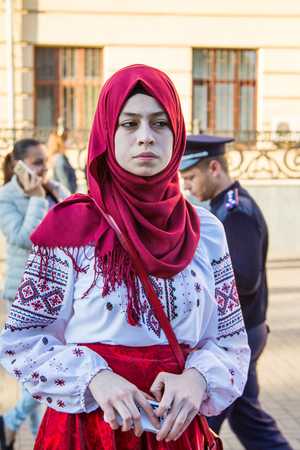ZaporizhiaUkraine- May 19, 2016: Young Muslim woman wearing Ukrainian traditional blouse waiting for the beginning of celebration of traditional Ukrainian embroidered clothes, known as vyshyvanka  day, celebrated in all regions of Ukraine every third Thu Редакционное