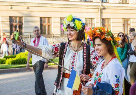 selfy: ZaporizhiaUkraine- May 19, 2016: girls in colorful flower wreaths taking photo on phone using selfy stick on celebration of national Ukrainian embroidered clothes, known as Vyshyvanka  Day