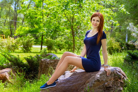 moccasins: Beautiful young smiling woman with long red hair wearing short casual blue dress and moccasins sitting on the rock in the park Stock Photo