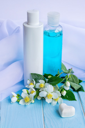 perfumed: Lotion and tonic in bottles, flowers, white cloths, heart shaped soap and beads - using jasmine essence for cosmetic products concept