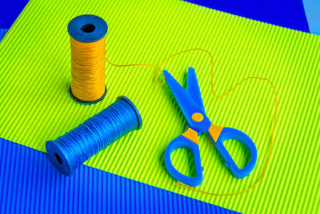 corrugate: Sewing spools of blue and yellow caprone threads, plastic scissors on colorful corrugate paper Stock Photo