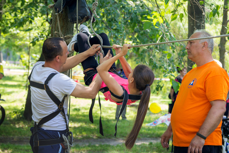 traverse: ZaporizhiaUkraine- June 5, 2016: teen girl training on tyrolean traverse fixed on trees under adult volunteers supervision on charity family festival organized in regions with most quantity of refugees from Donetsk area, occasioned with International Chi