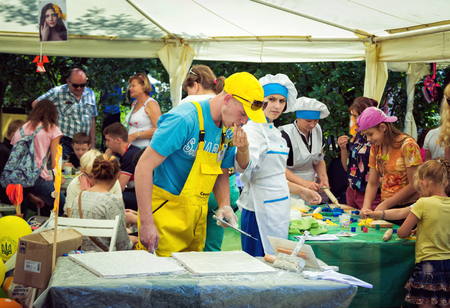 treating: ZaporizhiaUkraine- June 5, 2016: teen girl volunteer from cooking workshop treating biscuits her neighbor plasterer on charity family festival organized in regions with most quantity of refugees from Donetsk area, occasioned with International Children`s Editorial