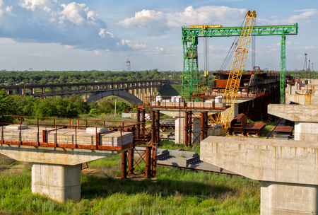 substructure: Abandoned incomplete arch bridge construction, cranes, concrete columns and rusty metal constructions Stock Photo