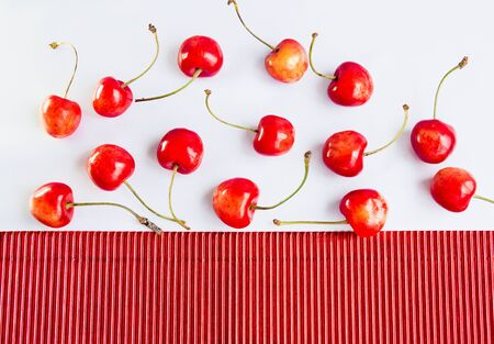 corrugate: ripe cherries and red corrugate cardboard paper and white tablecloth, abstract Stock Photo