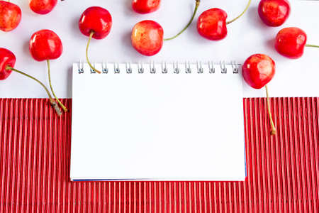 corrugate: Blank spiral notepad and ripe cherries on  red corrugate cardboard paper and white tablecloth, space for text or message Stock Photo