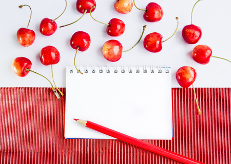 corrugate: Blank spiral notepad, pencil and ripe cherries on  red corrugate cardboard paper and white tablecloth, space for text or message
