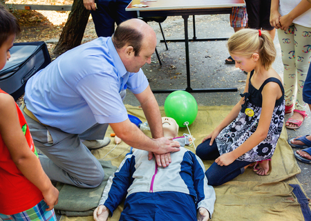 salvavidas: ZaporizhiaUkraine- September  3, 2016: Charity festival for children – City of professions . Instructor demonstrates  lifesaving CPR techniques on mannequin. Emergency training for children.
