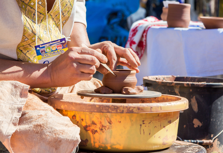 ZaporizhiaUkraine- September  17, 2016: Family festival of homemade pickled canned vegetables and preserves. Outdoors pottery workshop.  Closeup hands of potter, presenting  process of ceramic jug creating on a turning wheel. Editorial