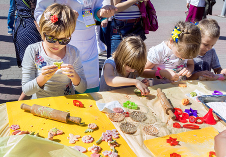 culinary skills: ZaporizhiaUkraine- September  17, 2016: Family festival of homemade pickled canned vegetables and preserves. Children activity –girls and boys making colorful paste figures for cookies decoration, outdoors workshop. Editorial