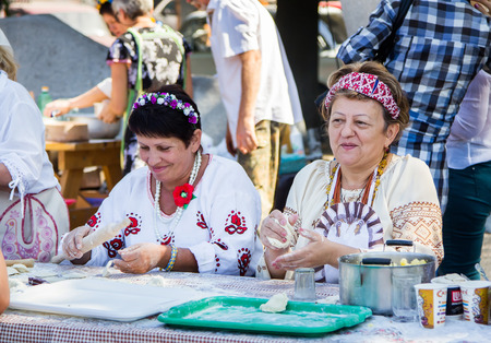 ZaporizhiaUkraine- September  17, 2016: Family festival of homemade pickled canned vegetables and preserves. Smiling women, wearing national Ukrainian clothing, making dumplings with mashed potatoes.  Outdoors cooking activity Editorial