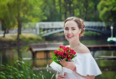 frilly: Portrait of happy beautiful smiling bride in white frilly dress with open shoulders, holding wedding bouquet of red roses, standing in a park