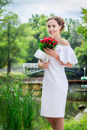 frilly: Portrait of happy beautiful smiling bride in white frilly dress whith open shoulders, holding wedding bouquet of red roses, standing in a park