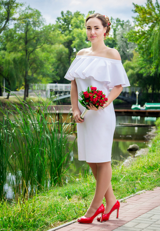 frilly: portrait of happy beautiful smiling bride in white frilly dress whith open shoulders, holding wedding bouquet of red roses, standing in a park Stock Photo