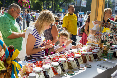 jams: ZaporizhiaUkraine- September  17, 2016: Family festival of homemade pickled canned vegetables and preserves. Mother and daughter  tasting jams and confitures near the stand with different sorts of sweet preserves in glass jars.
