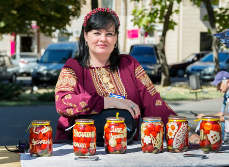 selfmade: ZaporizhiaUkraine- September 17, 2016: Family festival of homemade pickled canned vegetables and preserves.  Woman, wearing traditional Ukrainian embroidered blouse, presenting self-made canned tomatoes with  national symbols and patriotic words carved o