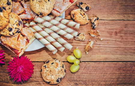 variety of sweet pastry - homemade jam pie, cream rolls and cookies with chocolate on a plate Stock Photo