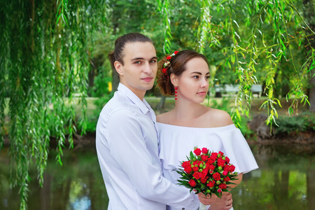 Happy loving wedding couple hugging   in the park with bouquet of red roses. Handsome young groom embracing beautiful bride in white dress near the pond